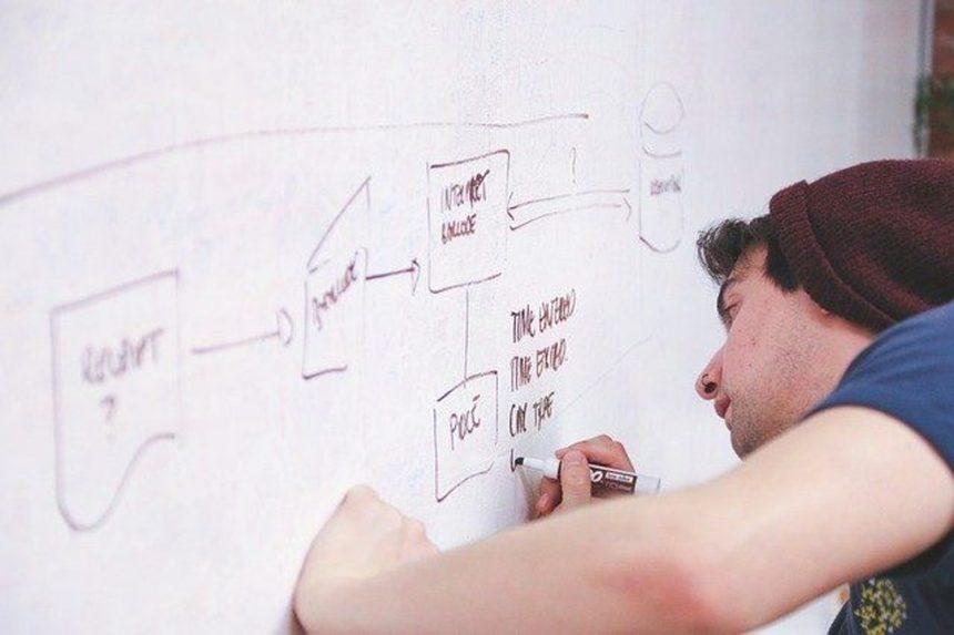 man drawing on wall